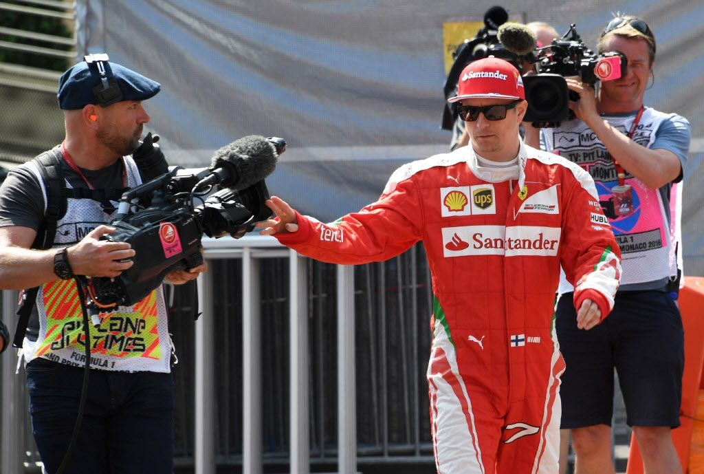 Ferrari's Finnish driver Kimi Raikkonen walks as he pushes away a camera during the third practice session at the Monaco street circuit, on May 28, 2016 in Monaco, one day ahead of the Monaco Formula 1 Grand Prix. / AFP PHOTO / PASCAL GUYOT auto auto-prix Horizontal CAR RACING F1 ORG XMIT: PG298
